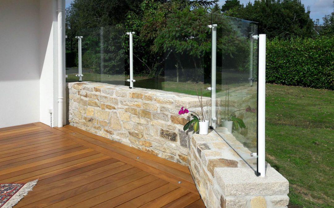 Pare-vent en verre sans cadre sur mur en pierres à Quimper.