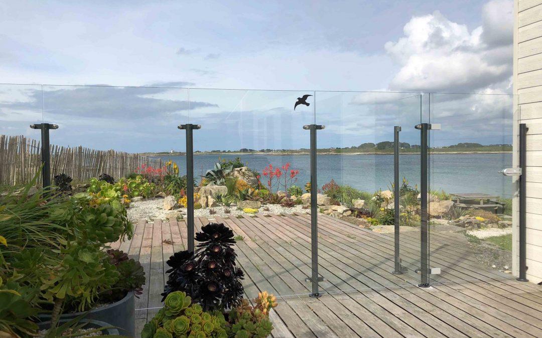 Pare-vent en verre sans cadre & portillon sur terrasse en bois bord de mer.